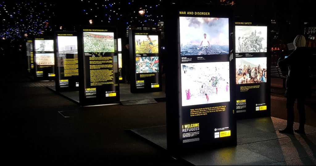 Back lit photography displayed in self standing display units, photographed at night.