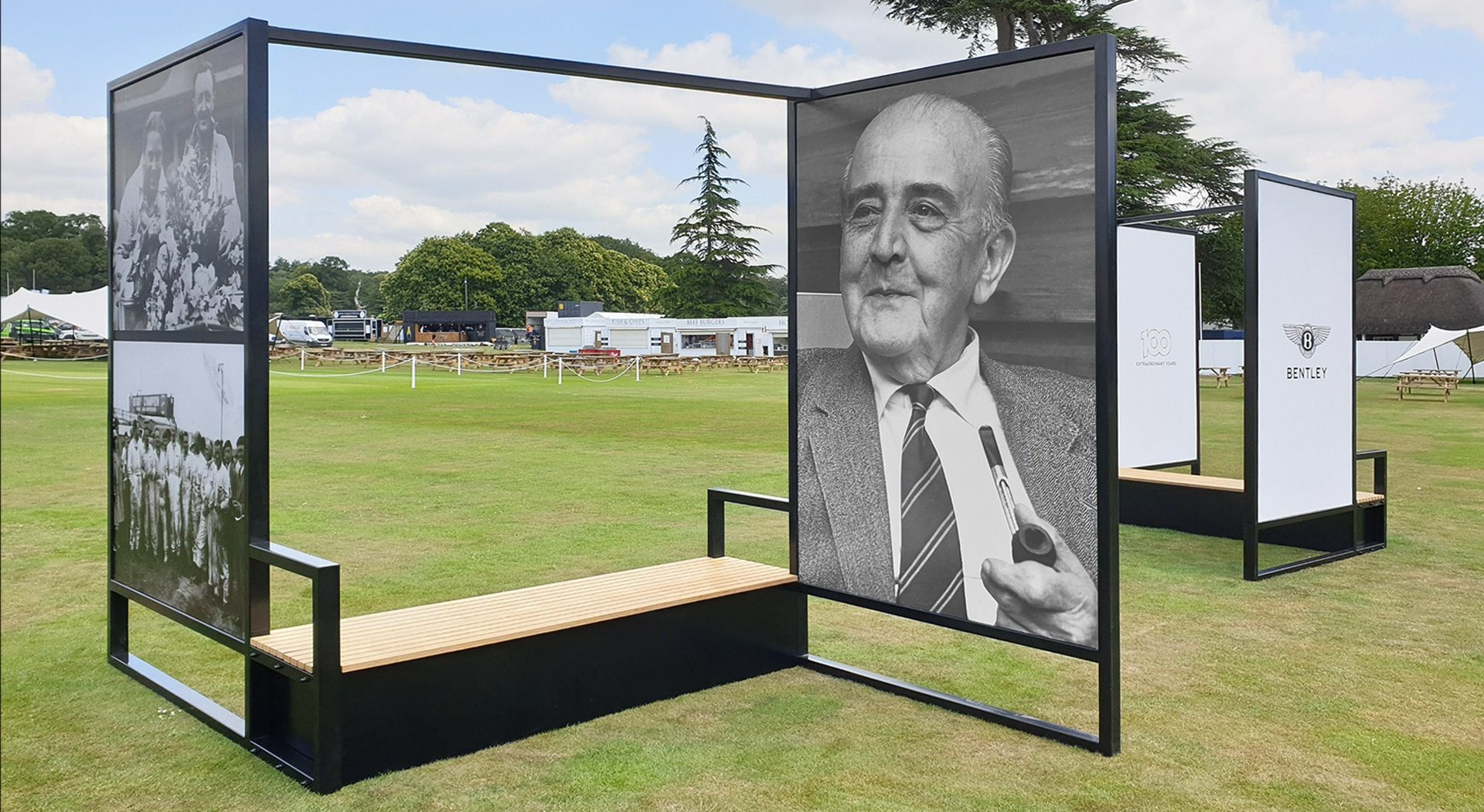 large format photographs displayed in metal frames with integrated seating, situated in grassy fields in Goodwood Festival of Speed