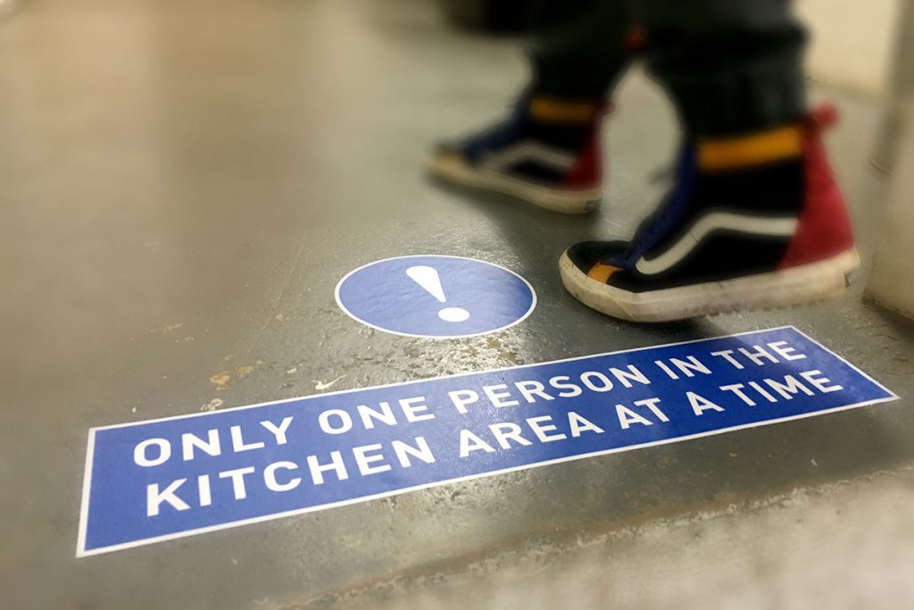 "COVID-19 social distancing sign ""only one person in the kitchen area at a time' floor vinyl sign"